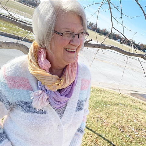 A Christopher & Banks customer wearing an Ombre scarf with a button front cozy stripe cardigan.