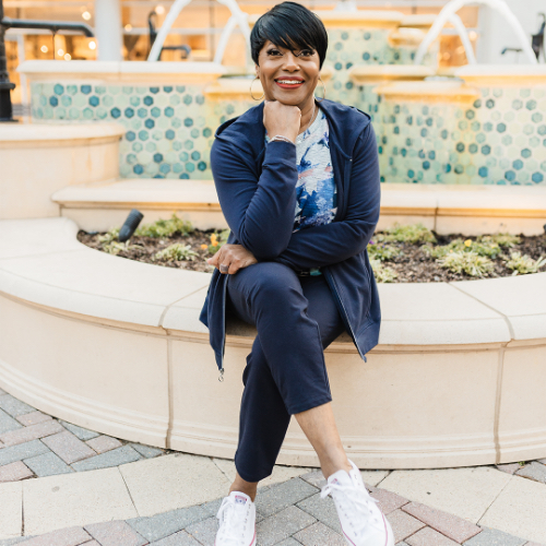 """A Christopher & Banks blogger, """"Janie"""", wearing a relaxed. RESTYLED.® Floral Print Twist Front Tee with a relaxed. RESTYLED.® Zip Up Hooded Jacket."""