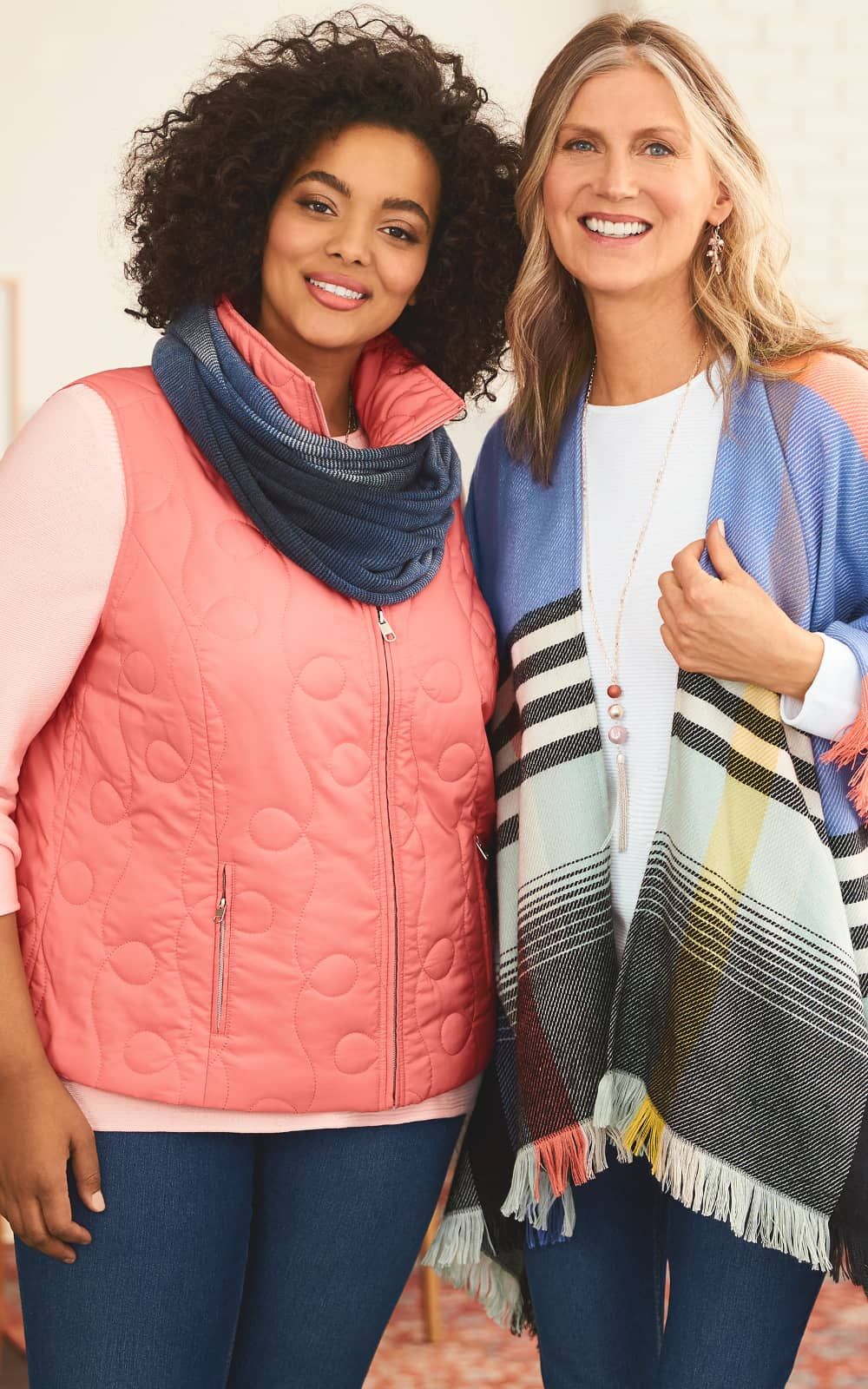 The Lovely Layers Outfit, on the left, featuring a three-quarters-sleeve essential top, solid swirl quilted vest, space dye knit loop scarf, and an everyday straight jean. The All Wrapped Up Outfit, on the right, featuring a three-quarters-sleeve essential top, striped fringe ruana, and jean legging.