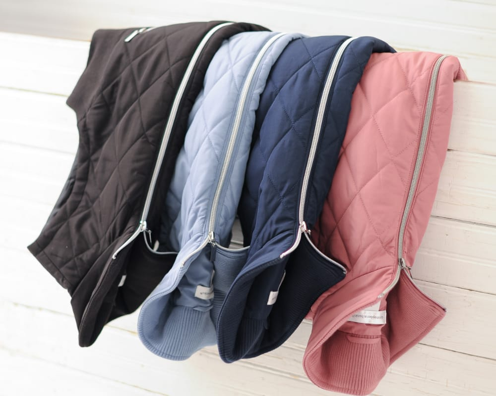 An array of our quilted vests in a variety of colors.
