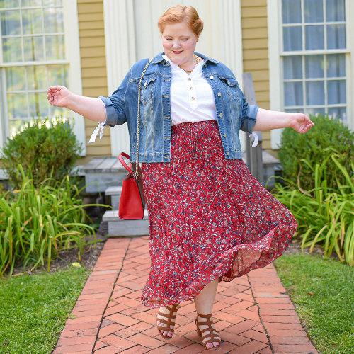 "A Christopher & Banks blogger, ""Liz"", wearing a Distressed Denim Jacket and a Ditsy Print Pleated Plus Size Maxi Skirt."